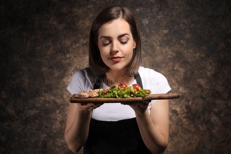 Cozinheiro chefe fêmea novo com o prato saboroso no fundo escuro imagem de stock royalty free
