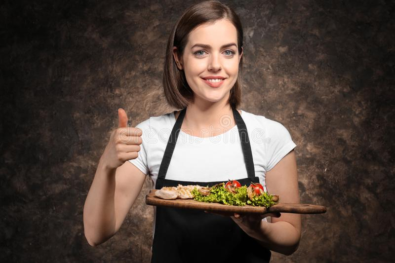 Cozinheiro chefe fêmea novo com o prato saboroso no fundo escuro fotos de stock