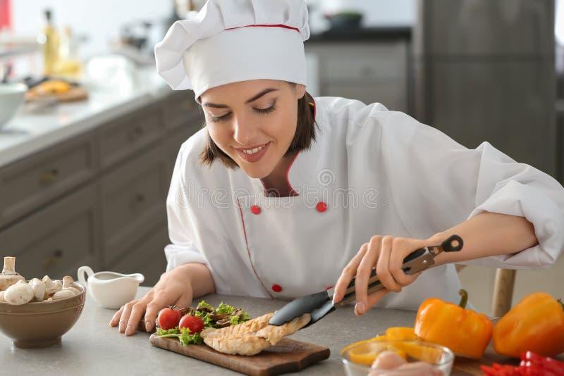 Cozinheiro chefe fêmea novo que põe o prato saboroso na placa de madeira sobre a mesa de cozinha imagens de stock