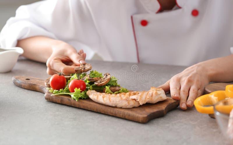 Cozinheiro chefe fêmea novo que põe o prato saboroso na placa de madeira sobre a mesa de cozinha, close up foto de stock royalty free