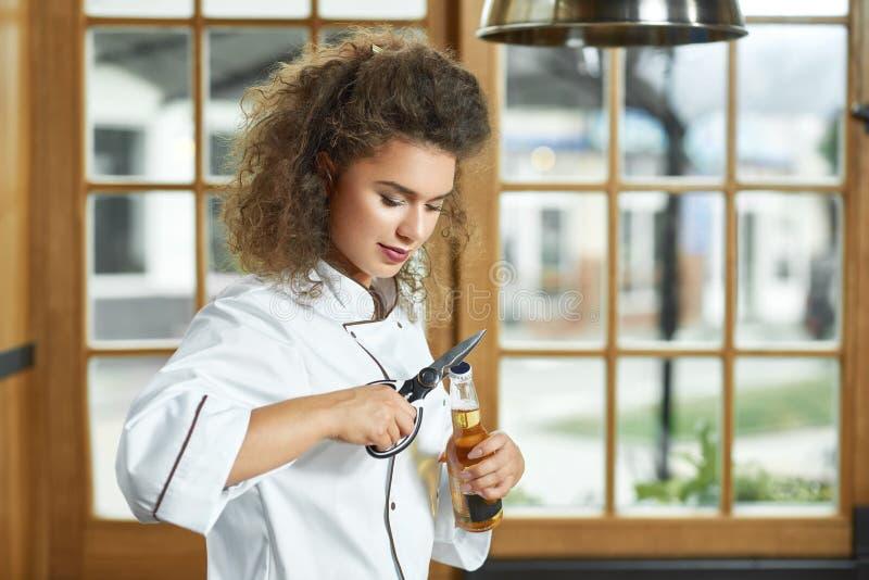 Cozinheiro chefe fêmea que abre uma garrafa da cerveja na cozinha foto de stock royalty free