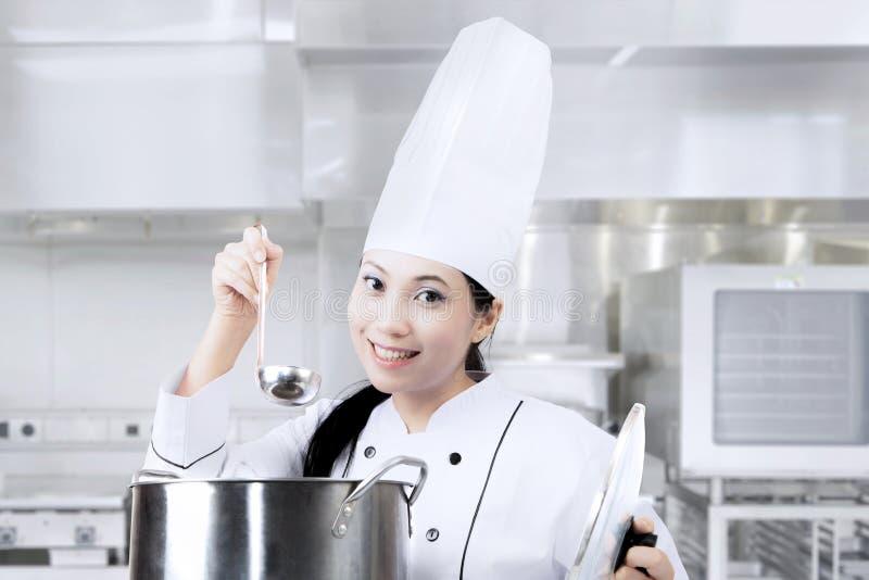 Cozinheiro chefe fêmea que cozinha com o potenciômetro na cozinha imagens de stock