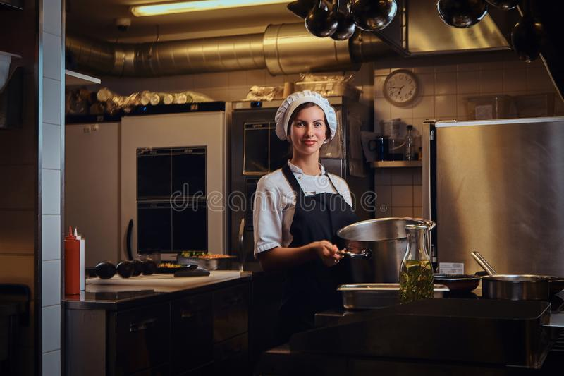 Cozinheiro chefe fêmea que veste um uniforme que guarda uma bandeja, sorrindo uma vista de uma câmera em uma cozinha fotos de stock royalty free