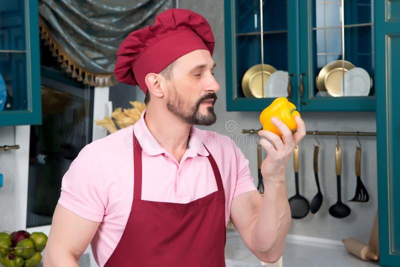 Cozinheiro chefe farpado no t-shirt cor-de-rosa que aspira a paprika amarela na cozinha foto de stock