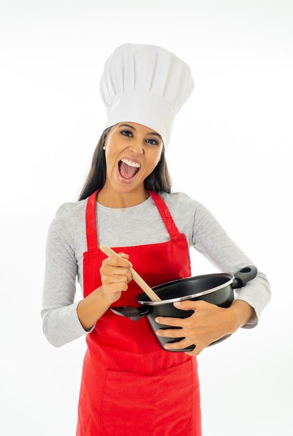 Cozinheiro chefe feliz bonito da jovem mulher que guarda uma colher de madeira e um potenciômetro com avental vermelho e o chapéu imagem de stock