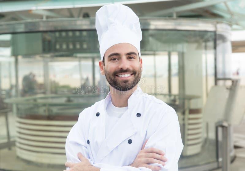 Cozinheiro chefe feliz com barba na frente de um restaurante imagens de stock royalty free