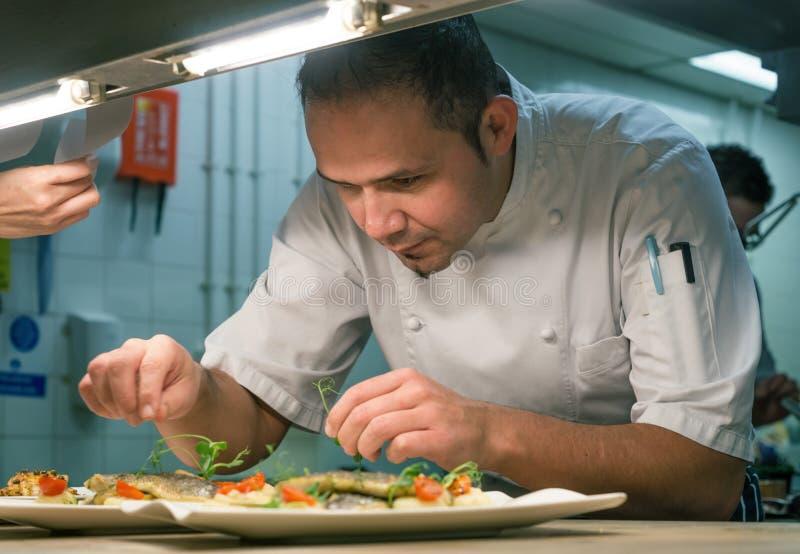 Cozinheiro chefe Garnishing Food na cozinha imagem de stock