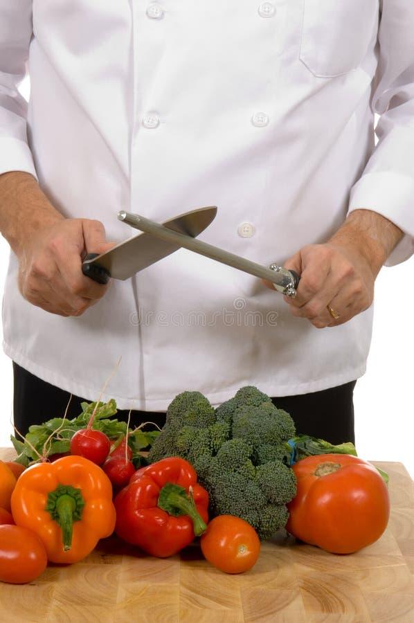 Cozinheiro chefe - homem que sharpening a faca imagens de stock