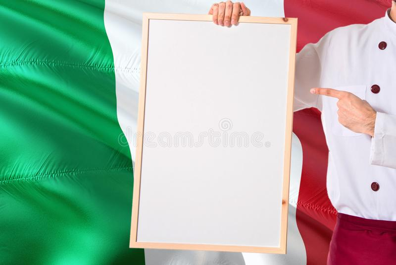 Cozinheiro chefe italiano que guarda o menu vazio do whiteboard no fundo da bandeira de Itália Cozinhe o uniforme vestindo que ap fotografia de stock royalty free