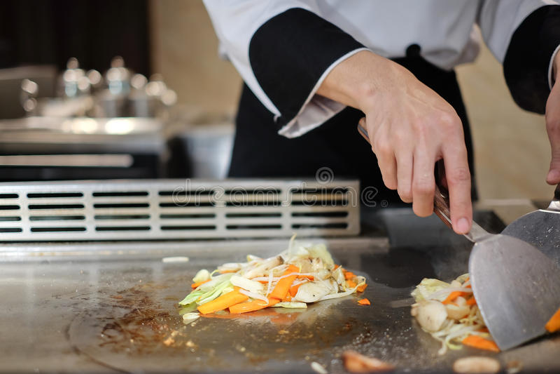 Cozinheiro chefe japonês deliberadamente que prepara e que cozinha o teppanyaki tradicional da carne fotografia de stock