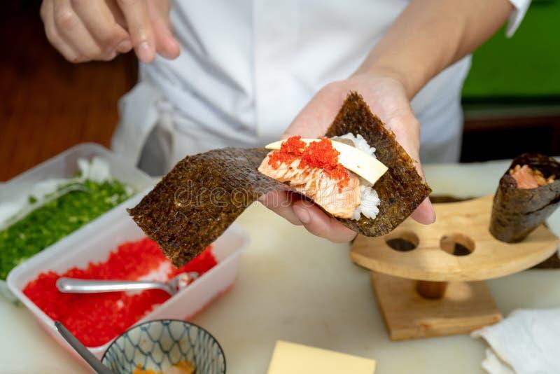Cozinheiro chefe japonês que faz o sushi no restaurante fotos de stock royalty free