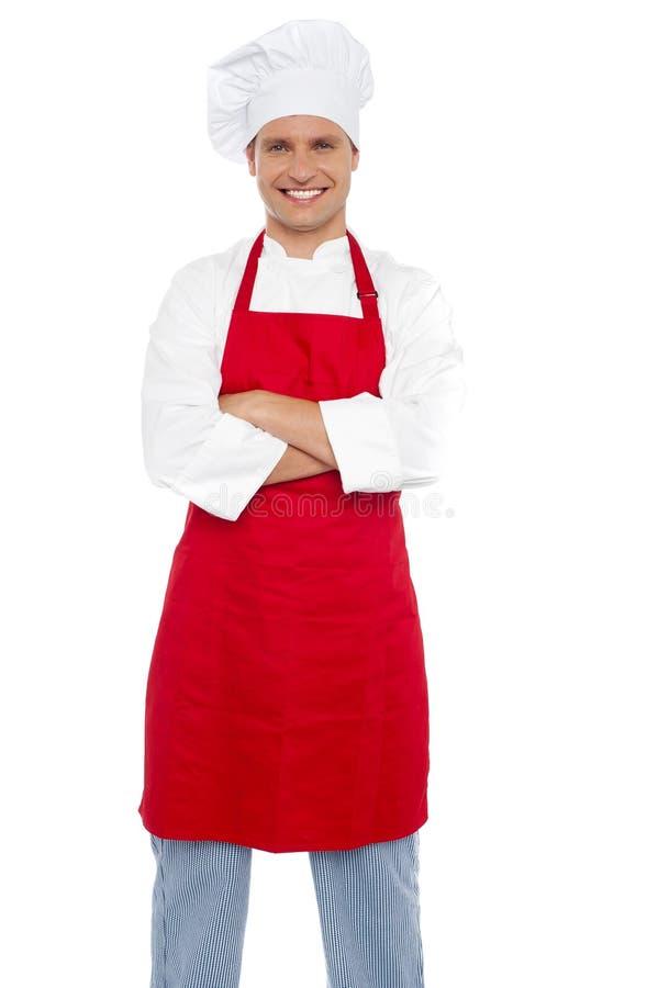 Cozinheiro chefe masculino alegre confiável com os braços cruzados imagens de stock royalty free