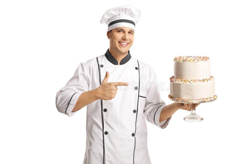 Cozinheiro chefe masculino alegre que guarda um bolo e que aponta nele foto de stock