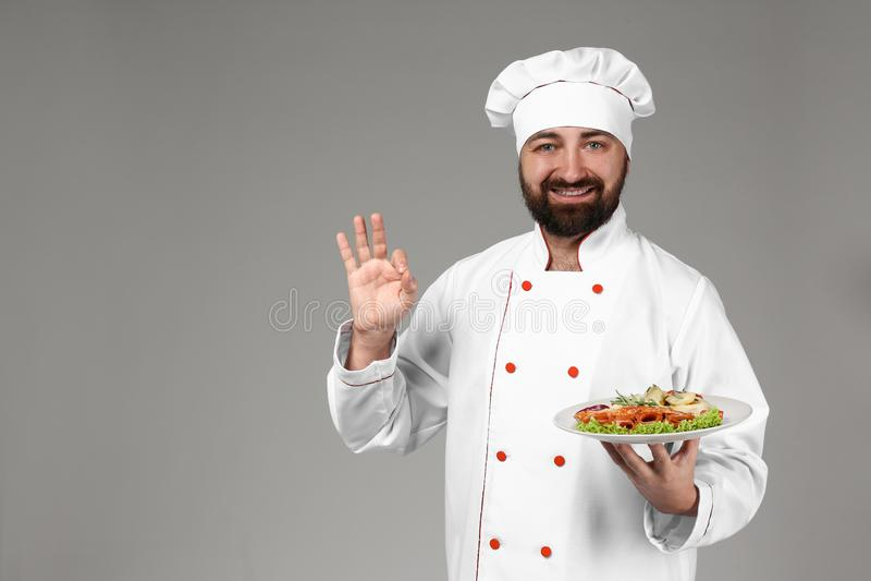 Cozinheiro chefe masculino com o prato saboroso no fundo cinzento fotografia de stock royalty free