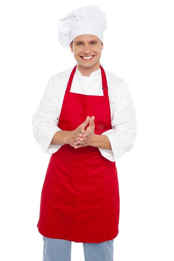 Cozinheiro chefe masculino confiável alegre no uniforme apropriado imagem de stock royalty free