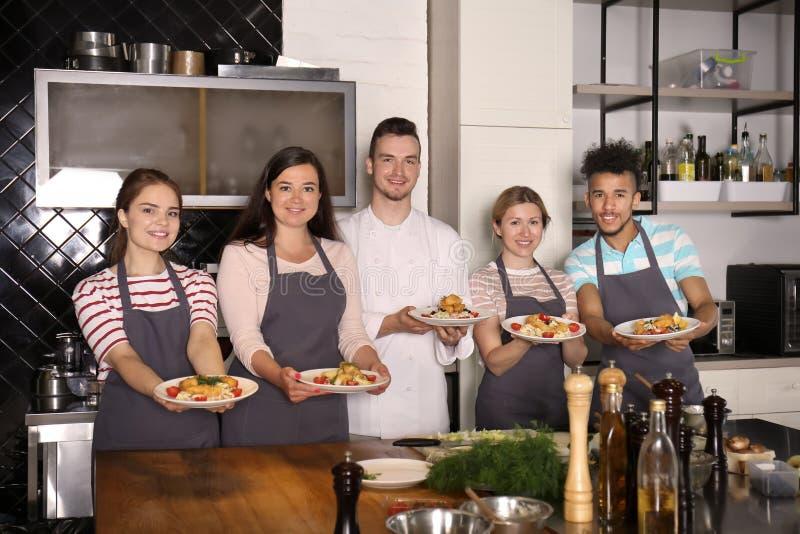 Cozinheiro chefe masculino considerável com os jovens que guardam placas com os pratos preparados durante aulas de culinária imagens de stock royalty free