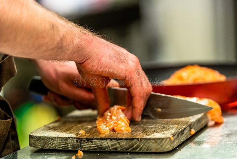 Cozinheiro chefe masculino Cutting Fresh Salmon na placa de madeira com borrado foto de stock