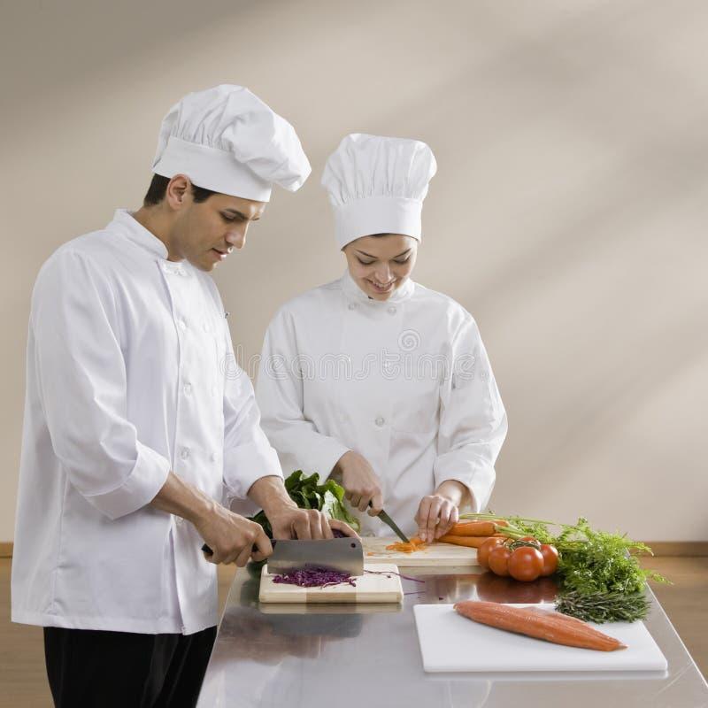 Cozinheiro chefe masculino e fêmea que desbasta vegetais fotos de stock royalty free