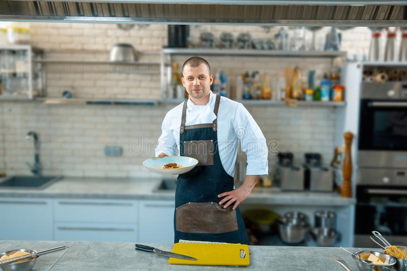 Cozinheiro chefe masculino feliz que apresenta o prato na cozinha comercial imagens de stock royalty free