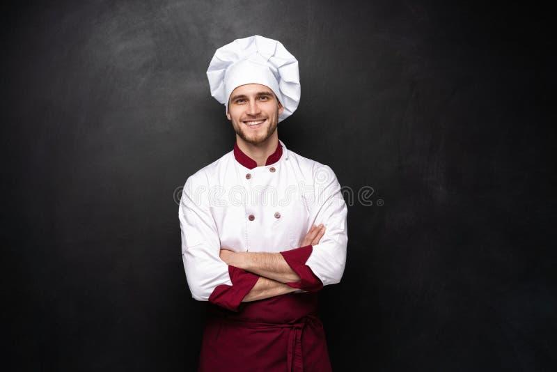 Cozinheiro chefe masculino novo isolado em um fundo preto imagens de stock