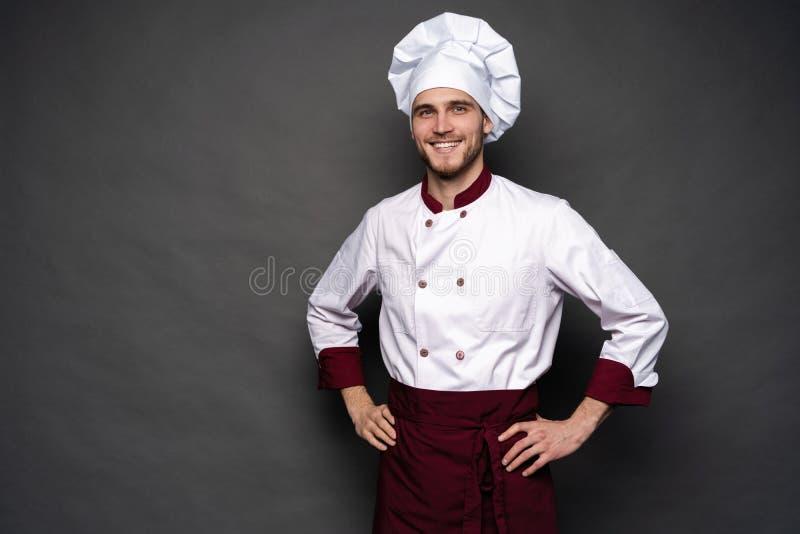 Cozinheiro chefe masculino novo isolado em um fundo preto imagem de stock