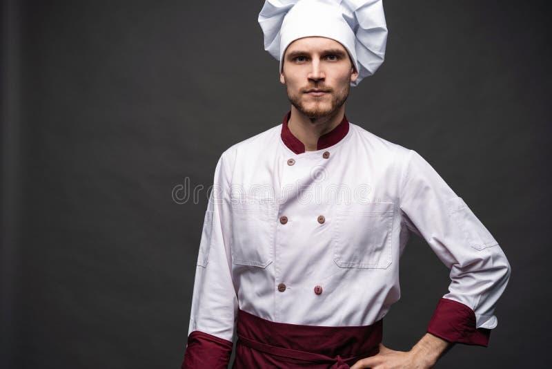 Cozinheiro chefe masculino novo isolado em um fundo preto imagem de stock royalty free