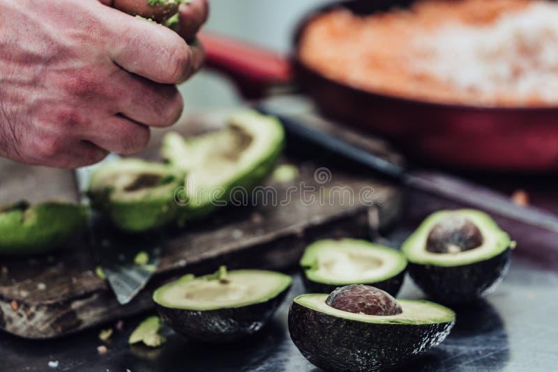 Cozinheiro chefe masculino Pealing Avocado para a refeição do casamento - a cozinha ajustou-se com ação, somente mãos do ` s do c imagem de stock royalty free