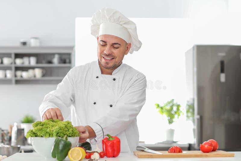 Cozinheiro chefe masculino que cozinha o prato saboroso na cozinha fotos de stock royalty free