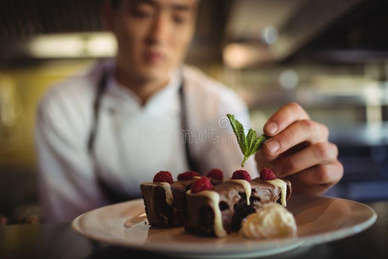 Cozinheiro chefe masculino que decora a placa de sobremesa imagens de stock royalty free