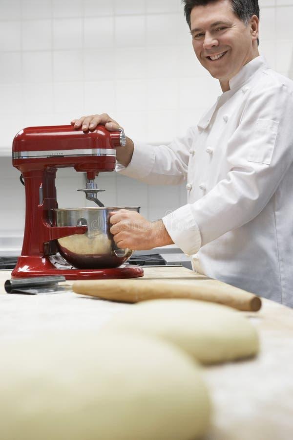 Cozinheiro chefe masculino Using Dough Mixer na cozinha foto de stock