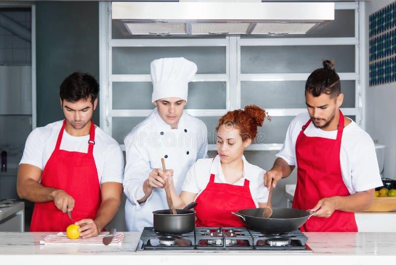 Cozinheiro chefe moderno que cozinha com a equipe na cozinha fotografia de stock royalty free