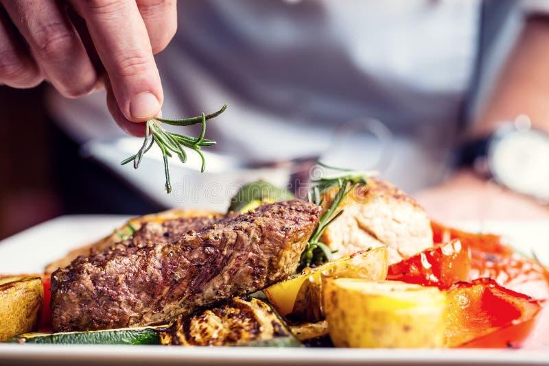 Cozinheiro chefe na cozinha do hotel ou do restaurante que cozinha somente as mãos Bife preparado com decoração vegetal fotos de stock