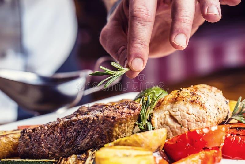 Cozinheiro chefe na cozinha do hotel ou do restaurante que cozinha somente as mãos Bife preparado com decoração vegetal imagem de stock