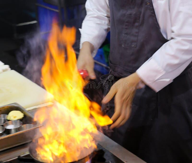 Cozinheiro chefe na cozinha do restaurante no fogão com a bandeja, fazendo o flambe no alimento fotografia de stock royalty free