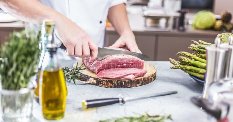 Cozinheiro chefe na cozinha do restaurante que cozinha, está cortando a carne ou o bife foto de stock royalty free
