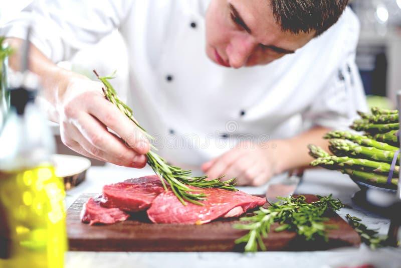 Cozinheiro chefe na cozinha do restaurante que cozinha, está cortando a carne ou o bife fotos de stock royalty free