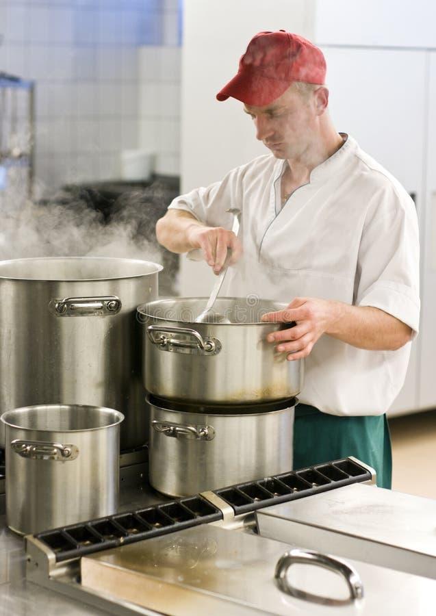 Cozinheiro chefe na cozinha industrial foto de stock
