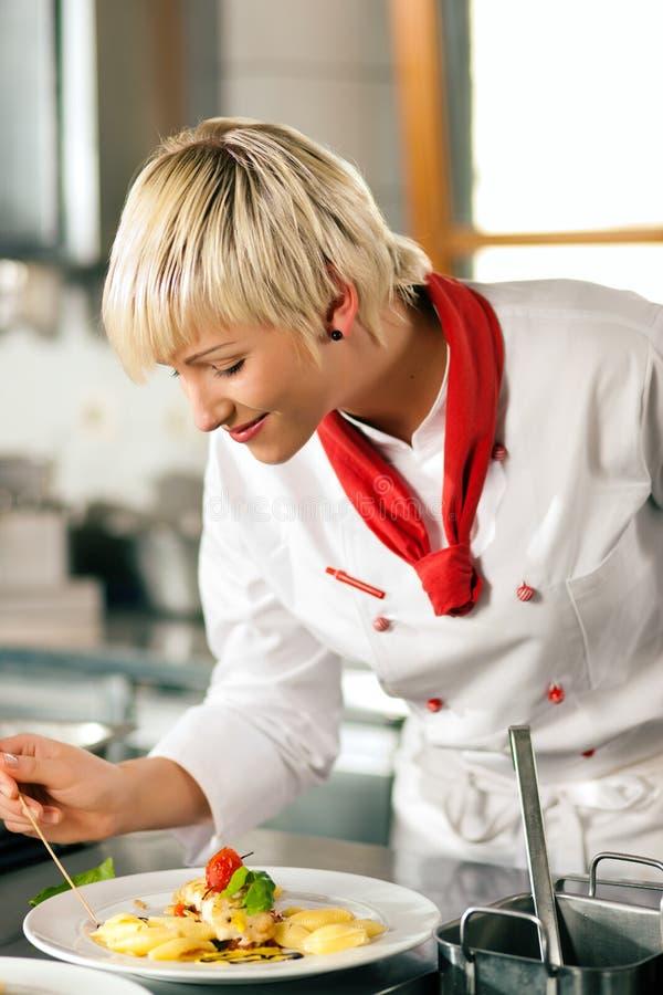 Cozinheiro chefe no cozimento da cozinha do restaurante fotografia de stock royalty free