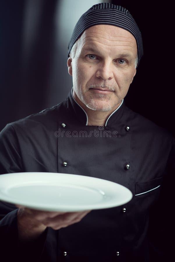 Cozinheiro chefe no uniforme preto que mostra uma placa foto de stock royalty free