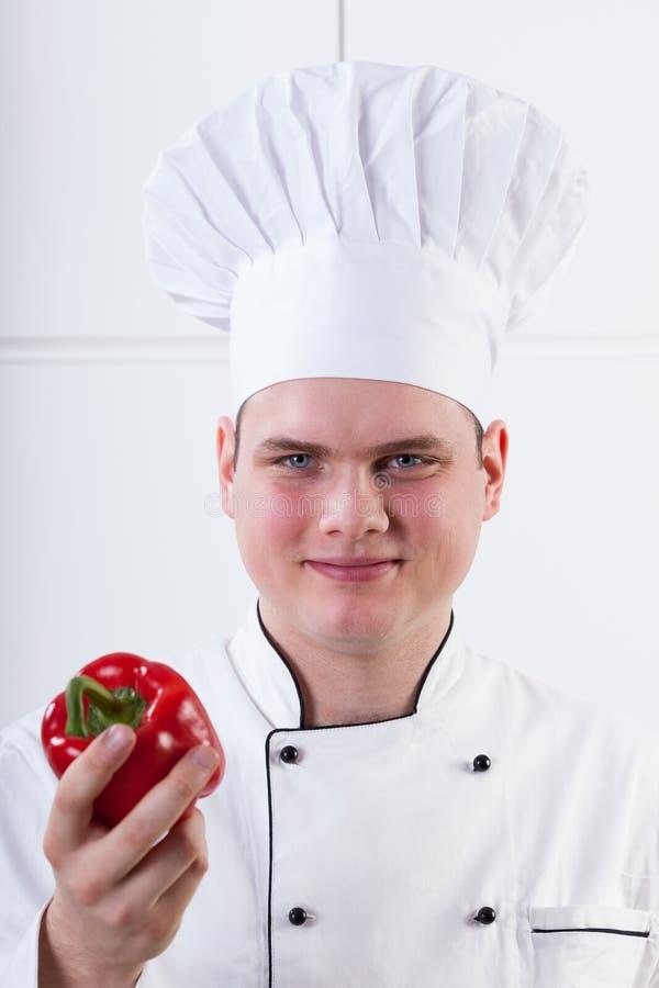 Cozinheiro chefe novo com pimenta foto de stock royalty free