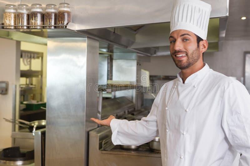 Cozinheiro chefe novo de sorriso que olha a câmera que mostra seu local de trabalho fotografia de stock