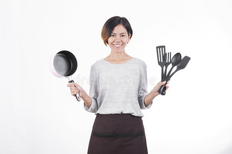 Cozinheiro chefe novo e dona de casa asiáticos que guardam a bandeja e a espátula fotografia de stock royalty free