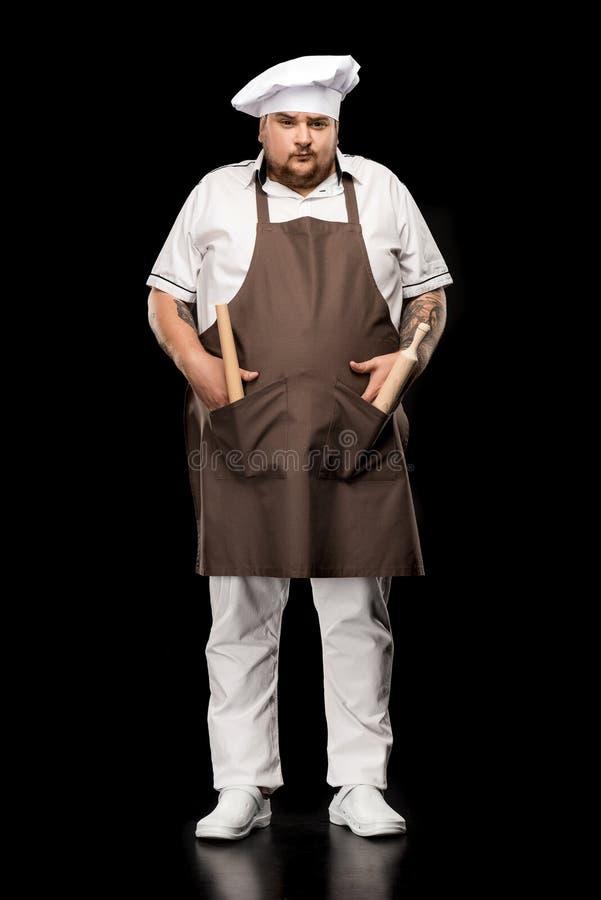 Cozinheiro chefe novo no chapéu que está com os bolsos dos pinos do rolo n do avental e que olha a câmera fotografia de stock