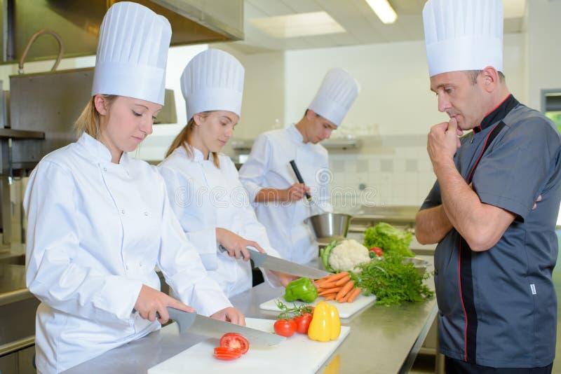 Cozinheiro chefe observando os estudantes fotos de stock royalty free