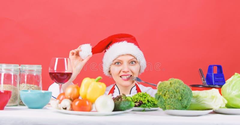 Cozinheiro chefe ou dona de casa da mulher que cozinham quando chap?u de Santa do desgaste As melhores receitas do Natal Conceito imagens de stock royalty free