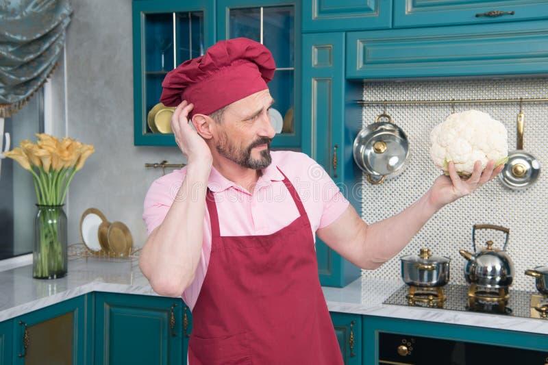 Cozinheiro chefe pensativo que olha de sobrancelhas franzidas ao olhar a couve-flor em sua mão fotos de stock
