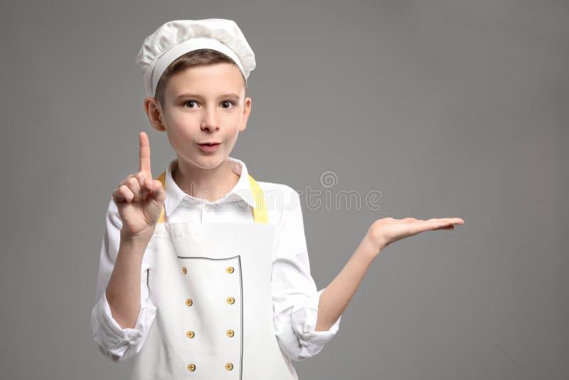 Cozinheiro chefe pequeno bonito com o indicador aumentado que guarda algo no fundo cinzento imagens de stock royalty free