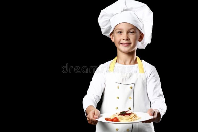Cozinheiro chefe pequeno bonito com o prato saboroso no fundo escuro fotografia de stock royalty free