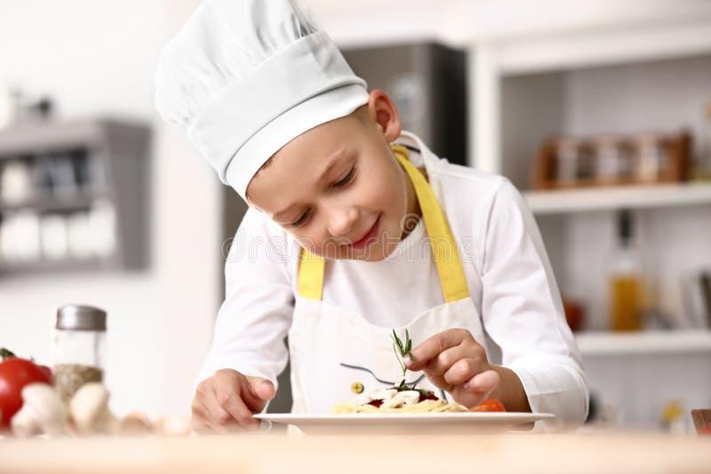 Cozinheiro chefe pequeno bonito que cozinha o prato saboroso na cozinha imagem de stock royalty free