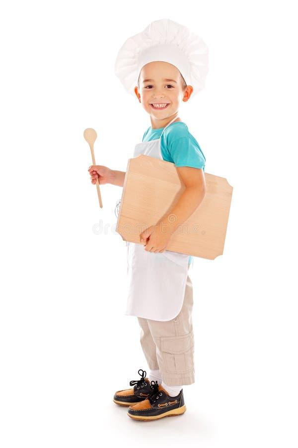 Cozinheiro chefe pequeno feliz com placa de madeira e colher fotos de stock